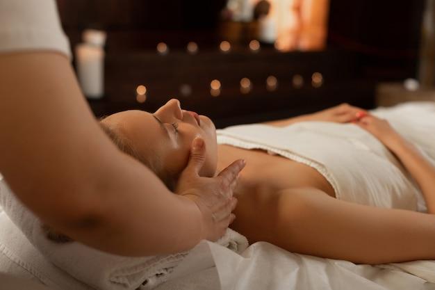 Overdekt ligbed. magere knappe dame die in een huiveringwekkende bui is terwijl de meester zich concentreert op een ontspannende massage