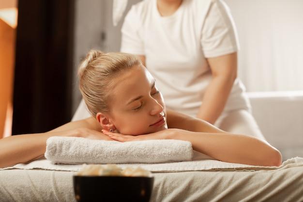 Overdekt massagebed. mooie vrouw met gesloten ogen die in vreedzame staat is tijdens ontspannende massage