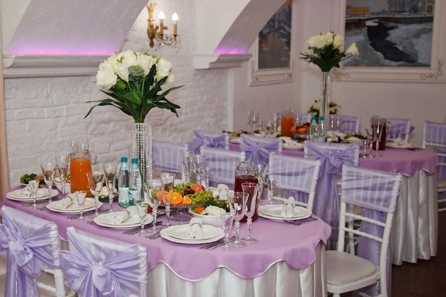 Overdekte zaal voor huwelijksrecepties met tafels en bloemdecoraties. feestrestaurant voor jonggehuwden en gasten. geweldig ontworpen interieur. luxe design voor evenementen. auteursrechtruimte voor site