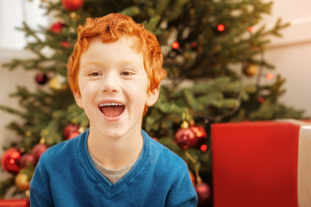 Overdosis opwinding. emotionele kleine jongen die zijn mond wijd open houdt terwijl hij opgewonden raakt en vrolijk lacht.