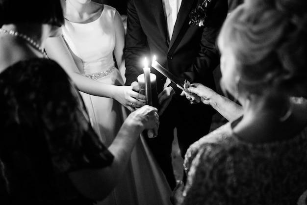 Overdracht van huwelijksvuur met behulp van kaarsen van moeders naar de pasgetrouwden