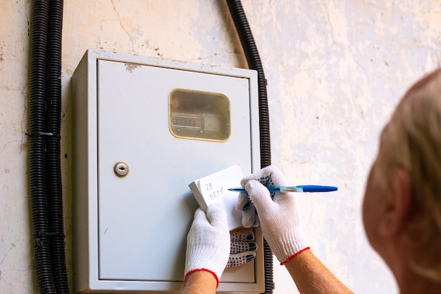 Overdracht van metingen van een elektrische meter. een man schrijft het aantal kilowatts op.