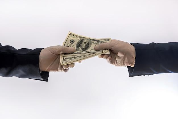 Overeenkomst tussen twee zakenlieden tijdens de coronavirusperiode, een man in handschoenen geeft geld aan een andere zakenman. veiligheidsconcept
