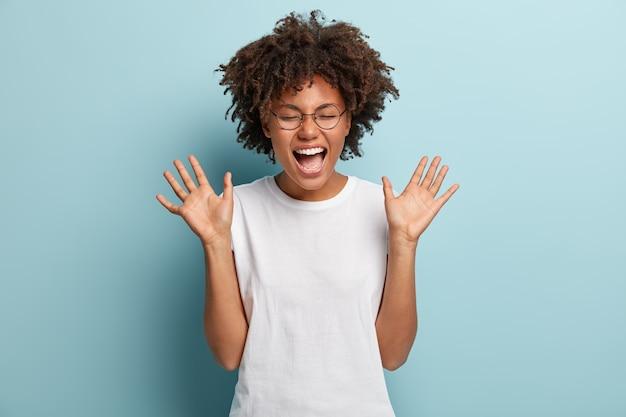Overemotieve afro-vrouw lacht luid, hoort grappige grap of verhaal, steekt tevreden de handpalmen op
