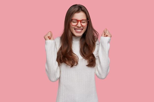 Overemotieve gelukkige jonge vrouw balde vuisten, blij om te winnen en kampioen te worden, draagt een optische bril en een witte trui