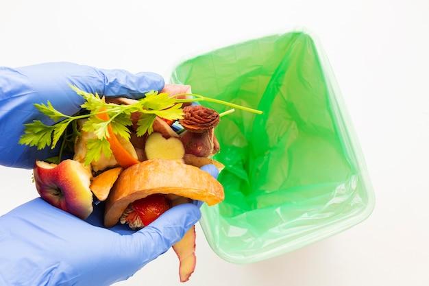 Overgebleven verspild voedsel en persoon die handschoenen draagt