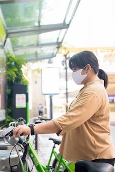 Overgewicht aziatische vrouw met masker met behulp van openbare fietsverhuur
