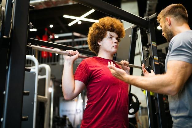 Overgewicht jonge mollige man die sportschool uitoefent met personal trainer