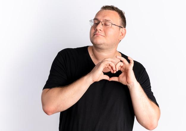 Overgewicht man in bril dragen zwart t-shirt hart gebaar met vingers gevoel positieve emoties staande over witte muur
