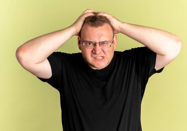 Overgewicht man in bril dragen zwart t-shirt lookign camera met boos gezicht gaan wild trekken zijn haar over licht