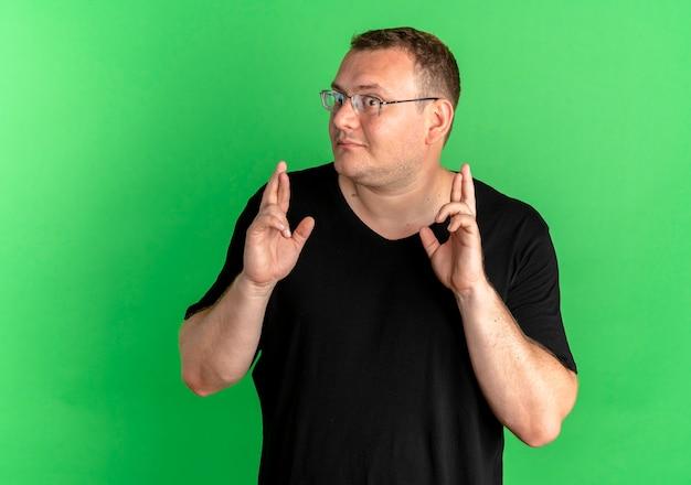 Overgewicht man in bril dragen zwart t-shirt wenselijke wens kruising vingers met blij gezicht over groen