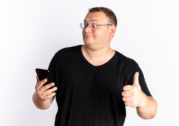 Overgewicht man in bril met zwart t-shirt kijken naar zijn smartphonescherm met duimen omhoog staande over witte muur