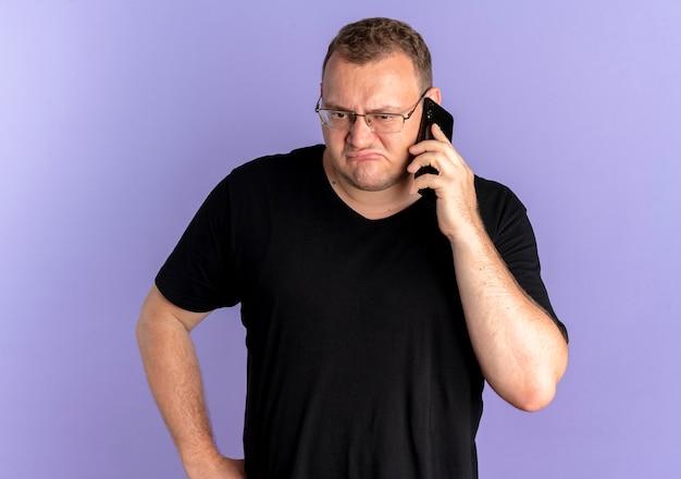 Overgewicht man in bril met zwarte t-shirt op zoek verward en ontevreden tijdens het praten over de mobiele telefoon over blauw
