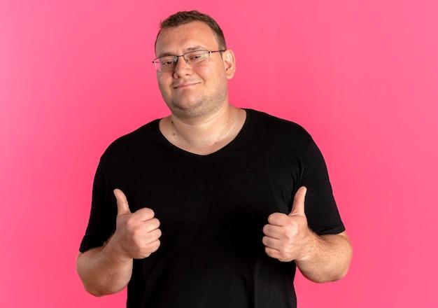 Overgewicht man in glazen dragen zwarte t-shirt glimlachend duimen opdagen over roze