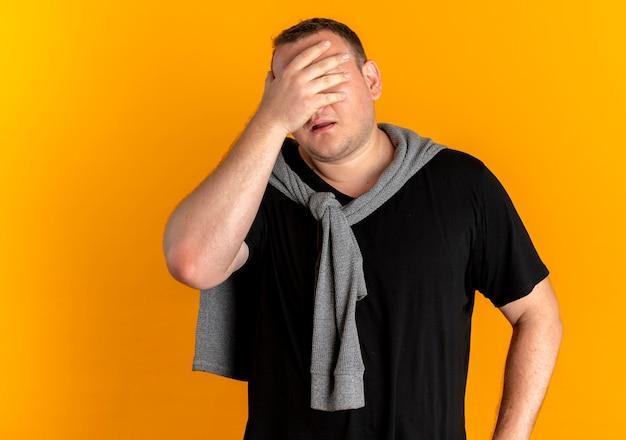 Overgewicht man in glazen met zwart t-shirt die gezicht bedekt met hand moe en verveeld staande over oranje muur