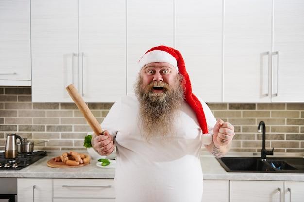 Overgewicht man in kerstmuts met een houten deegroller aan de ene hand en balt zijn vuist