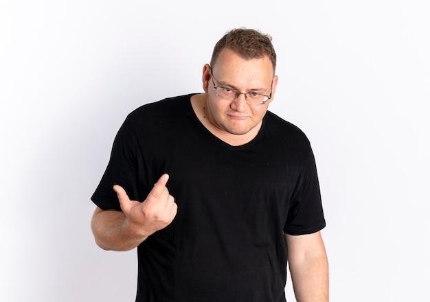 Overgewicht man met zwarte t-shirt in glazen op zoek verward met wijsvinger staande over witte muur