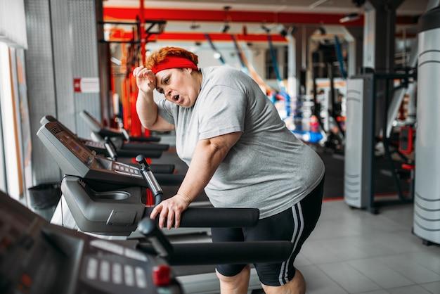Overgewicht vermoeide vrouw draait op een loopband in de sportschool. calorieën branden, zwaarlijvige vrouwelijke persoon in sportclub