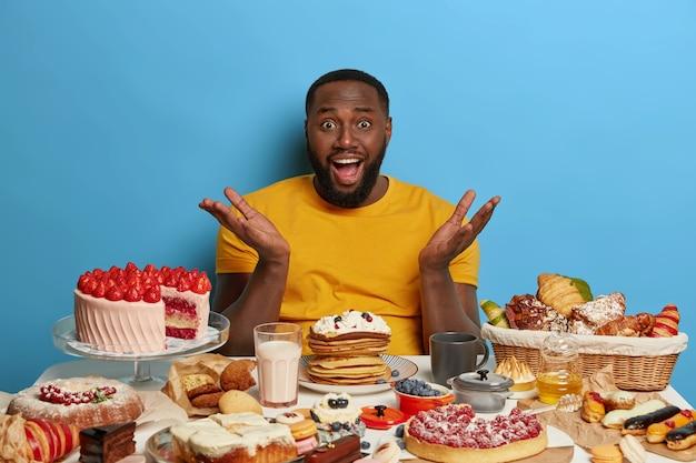 Overgewicht verslaafd aan suiker bebaarde man heeft een verbaasde uitdrukking, spreidt zijn handpalmen, kan niet wachten om desserts te eten, omringd door lekkere taarten, koekjes en melk