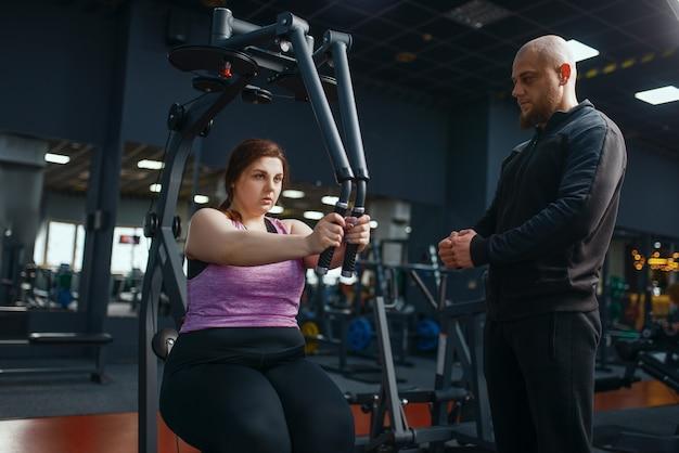 Overgewicht vrouw doet oefening in de sportschool, training met instructeur