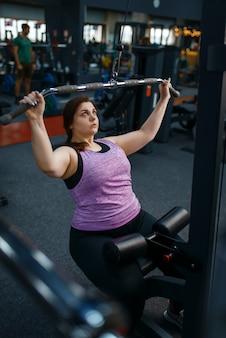 Overgewicht vrouw doet oefening in sportclub, actieve training