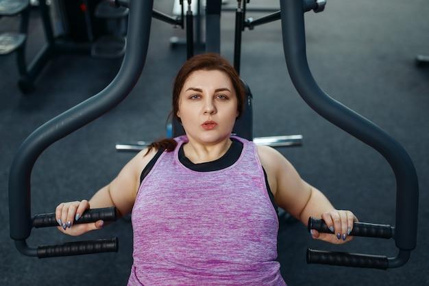 Overgewicht vrouw op fitnessapparaat in sportschool, bovenaanzicht, actieve training