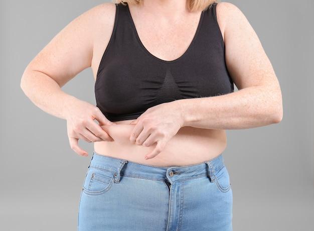 Overgewicht vrouw op grijze achtergrond, close-up
