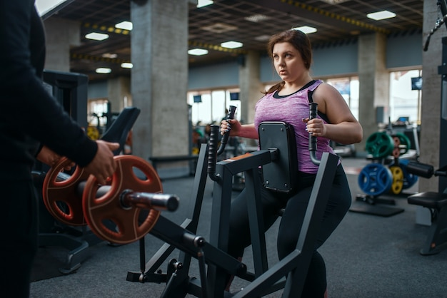Overgewicht vrouw op hometrainer in sportschool, training met instructeur