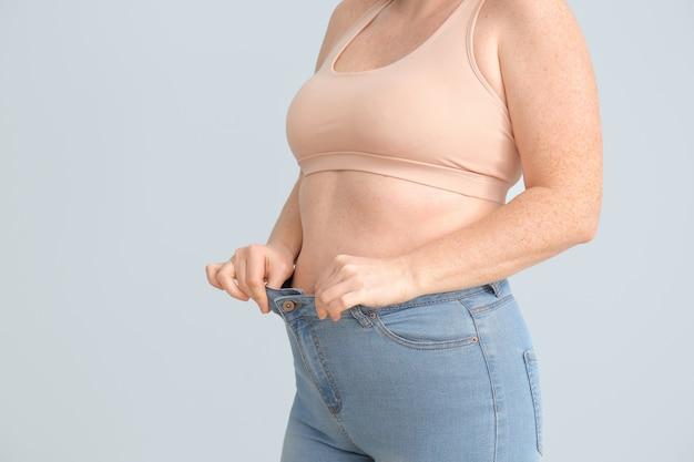 Overgewicht vrouw op kleur oppervlak, close-up