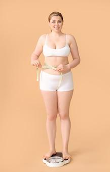 Overgewicht vrouw staande op schalen tegen gekleurde achtergrond.