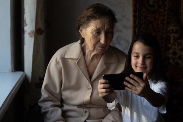 Overgrootmoeder zit met achterkleindochter en kijkt in de smartphone. oma en kind nemen een selfie op een smartphone. grootmoeder met haar kleindochter kijken in de telefoon.