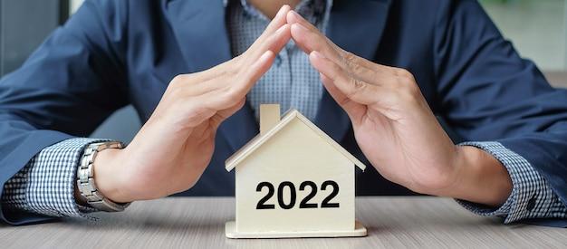 Overhandigt houten huismodel met 2022 nieuwjaarstekst