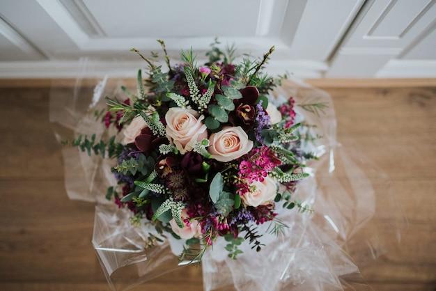 Overhead close-up shot van een bruiloft bloemboeket op een houten vloer
