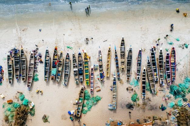 Overhead luchtfoto van verschillende gekleurde boten op een zandstrand met de zee in de buurt