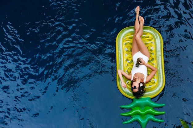Overhead portret van innemend meisje dat in pool zwemt. prachtige blanke gelooide vrouw weekend doorbrengen in zomerverblijf.