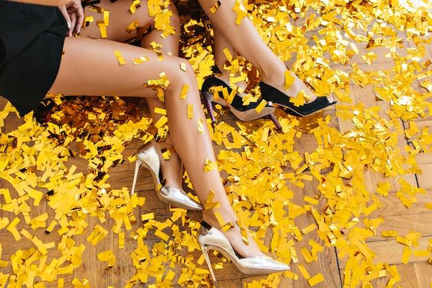 Overhead portret van vrouwen die elegante schoenen met hoge hakken dragen en tijdens het feest op de vloer zitten
