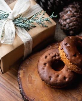 Overhead schot van chocolade-gedoopte donuts op een houten bord naast een ingepakte geschenkdoos