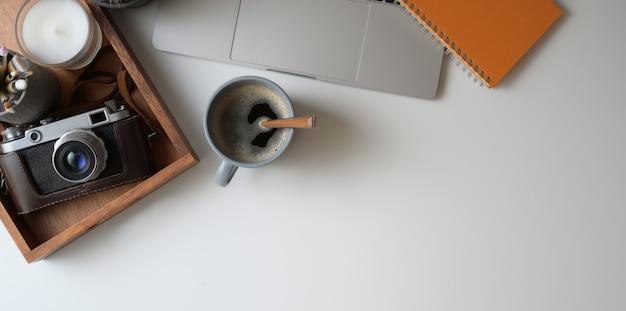 Overhead schot van comfortabele werkruimte met laptop, camera, koffiekopje en kantoorbenodigdheden op wit bureau