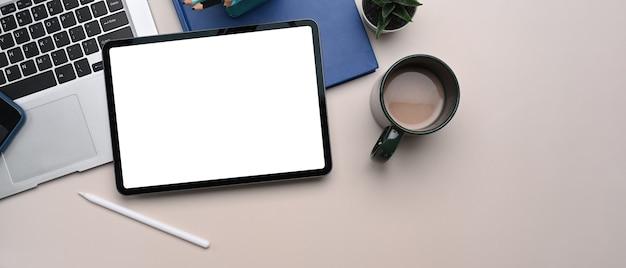 Overhead schot van digitale tablet met leeg scherm, laptop, koffiekopje en notebook op beige crème achtergrond.