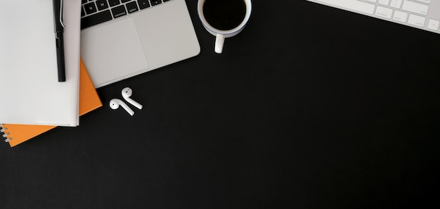 Overhead schot van donkere trendy werkplek met laptop en kantoorbenodigdheden op zwarte tafel