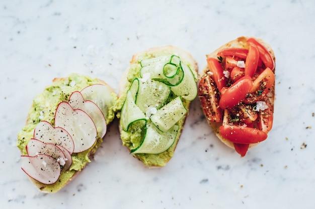 Overhead schot van drie heerlijke sandwiches met avocadosaus op een marmeren achtergrond