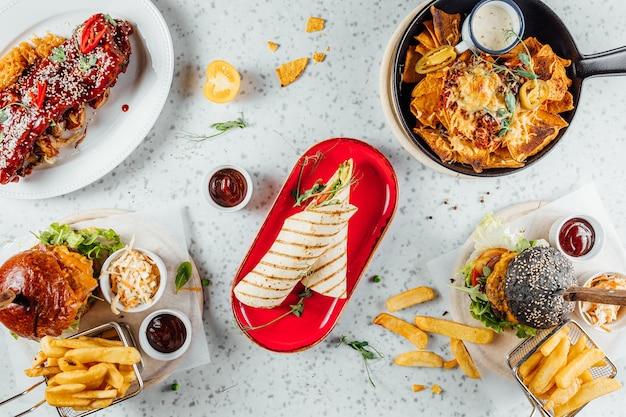 Overhead schot van een verscheidenheid aan fastfood en sauzen op tafel