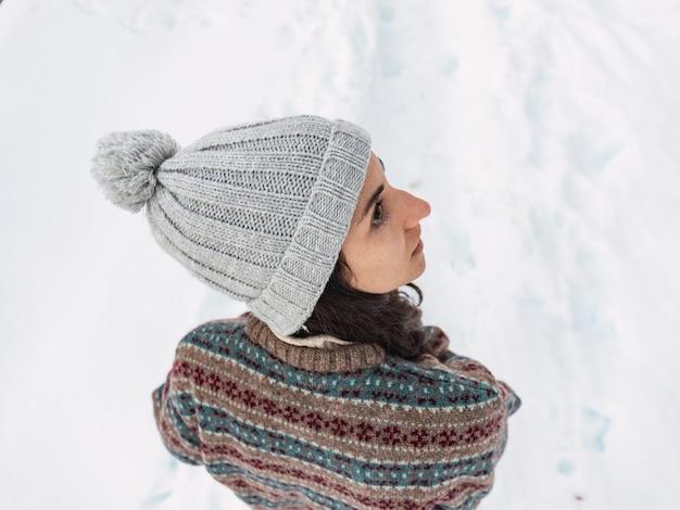 Overhead schot van een vrij jong meisje in de sneeuw gekleed in winterkleding