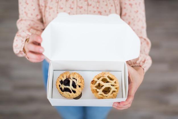Overhead schot van een vrouwtje met een witte doos met twee kleine gebakjes