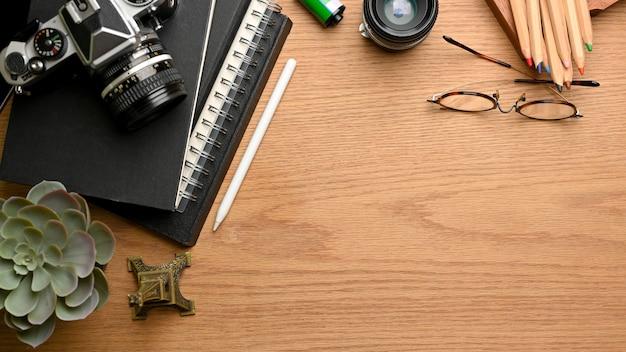 Overhead schot van houten tafel met briefpapier camera bril plant pot en kopie ruimte