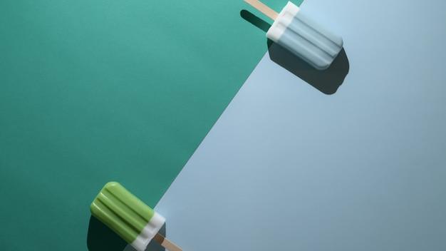 Overhead schot van limoen en blauwe frambozen smaak ijslollys op plat lag groene en blauwe achtergrond
