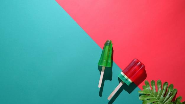 Overhead schot van limoen en citroen smaak ijslollys, blad en kopie ruimte op plat lag rode en groene achtergrond