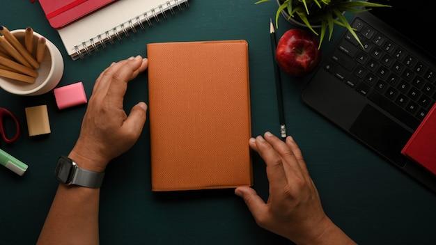 Overhead schot van mannelijke handen met boek op donkergroene studie tafel