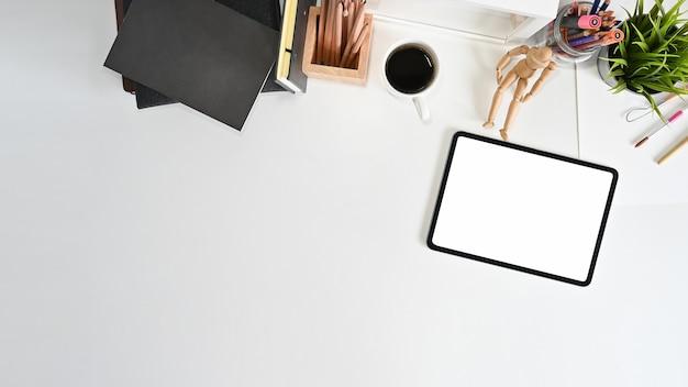 Overhead schot van mockup tablet, koffie en kantoorbenodigdheden op kantoor tafel.