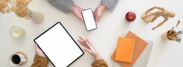 Overhead schot van ondernemers bespreken over hun project met digitale apparaten